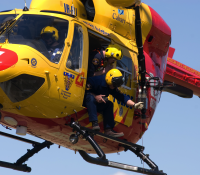 Westpac Rescue Helicopter in flight with crew member operating winch