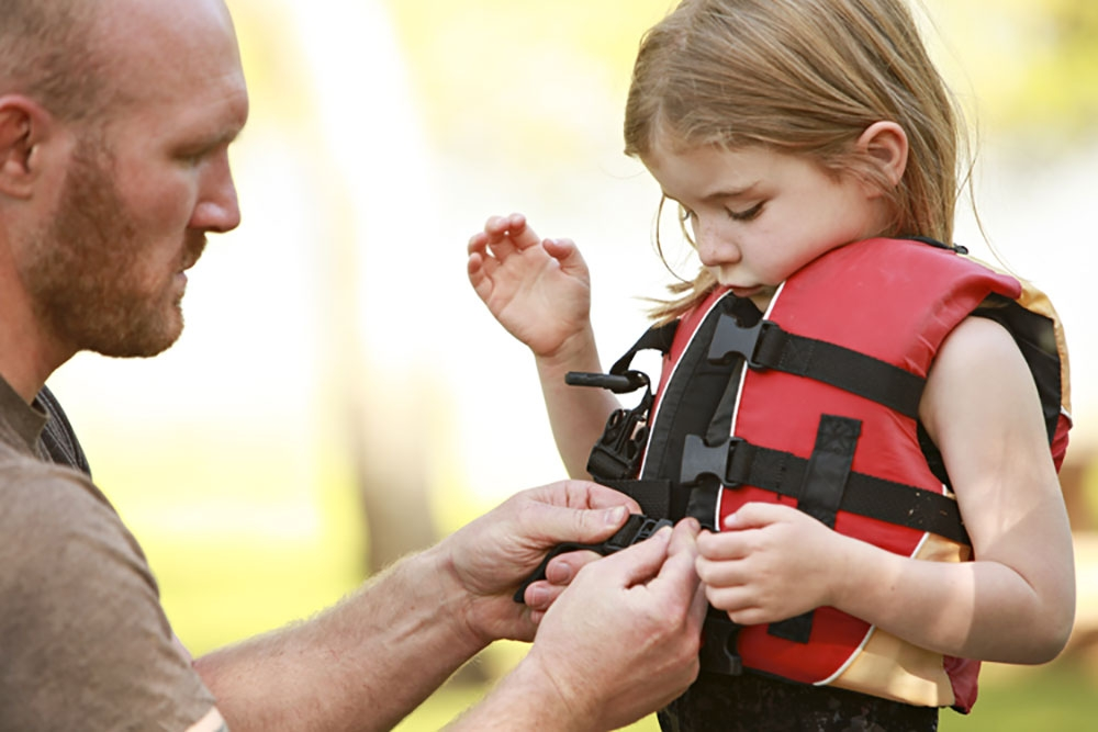 Dad fitting life jacket to his daughter.